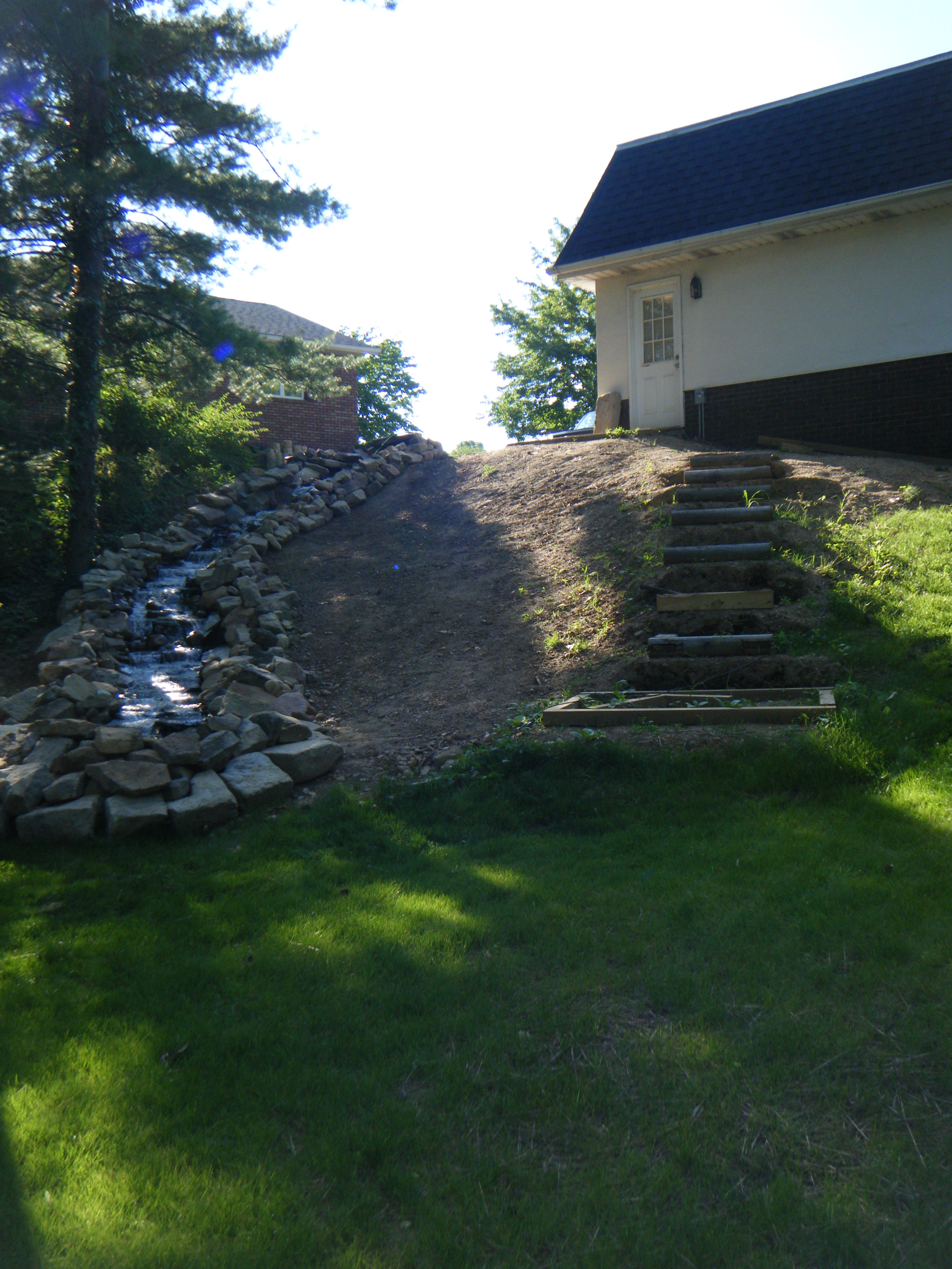 Backyard waterfall down a hill with custom steps
